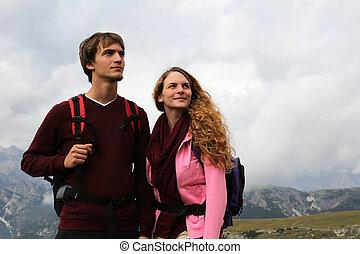jong paar, kijkend, in de bergen