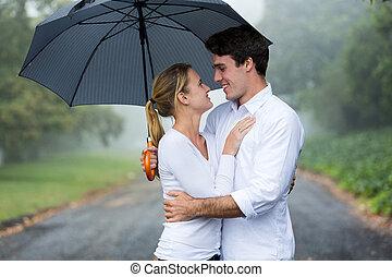 jong paar, met, paraplu, in de regen