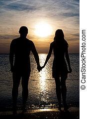 jong paar, silhouette, op, een, zee, strand, holdingshanden, en, kijken naar, ondergaande zon , onder, de, zee
