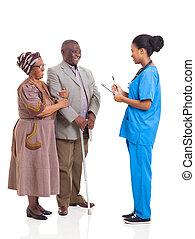 jonge, afrikaan, medisch, verpleegkundige, en, oudere paar, patiënt