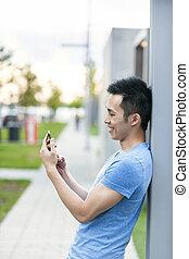 jonge, aziatische man, met, mobiele telefoon