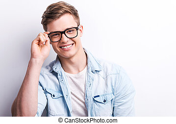 jonge, en, creative., mooi, jonge man, aanpassen, zijn, eyewear, en, het glimlachen, terwijl, staand, tegen, grijze , achtergrond.