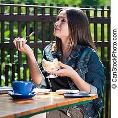 jonge, gelukkige vrouw, in, koffiehuis, eten, ijs