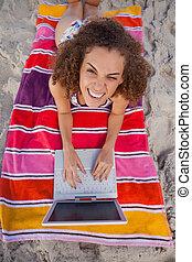 jonge, glimlachende vrouw, kijken naar van het fototoestel, terwijl, gebruik, haar, draagbare computer, op het strand