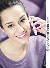 jonge, glimlachende vrouw, op telefoon