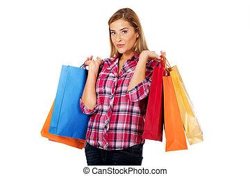 jonge, glimlachende vrouw, vasthouden, het winkelen zakken