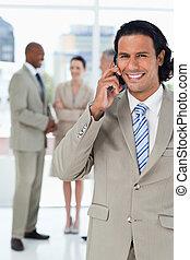 jonge, het glimlachen, uitvoerend, het spreken op de telefoon, en, met, zijn, team, achter, hem