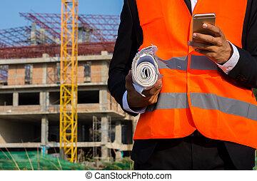 jonge, ingenieur, in, oranje overhemd, stalletjes, vasthouden, een, bouwschets, en, het spreken op een beweeglijk, telefoon., op, gebouw, met, kranen, in, de, achtergrond.