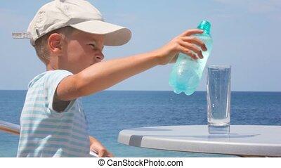 jonge jongen, gietend water, van, fles, in, glas, en, drinkt
