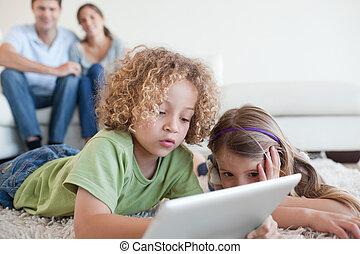 jonge kinderen, gebruik, een, tablet, computer, terwijl, hun, vrolijke , ouders, zijn, schouwend, in, hun, woonkamer