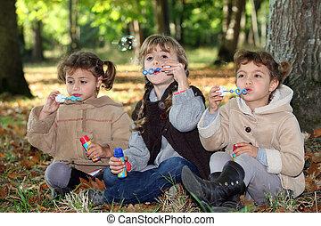 jonge kinderen, zeepbellen, in, de, hout
