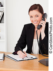 jonge, knappe , rode-haired vrouw, in, kostuum, schrijvende , op, een, notepad, en, telefoneren, terwijl, zittende , in, een, kantoor