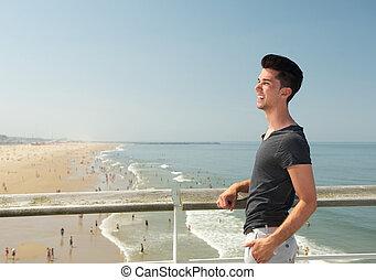 jonge man, het glimlachen, aan het strand