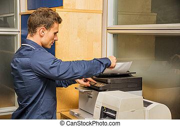 jonge man, het werken, fotokopieerapparaat, machine
