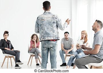jonge man, in, denim, uitrusting, het spreken, om te, groepering van tieners, met, problemen, gedurende, therapie