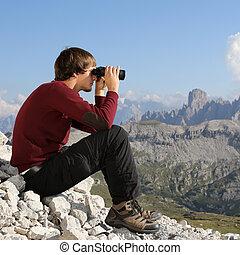 jonge man, kijkend door verrekijkers, in de bergen