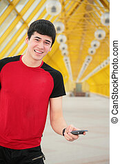 jonge man, met, mobiele telefoon, op, gele, voetbrug