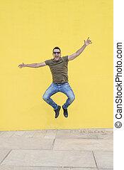 jonge man, met, zonnebrillen, het springen in, voorkant, van, een, gele, wall.