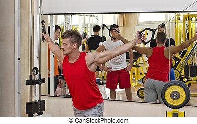 jonge man, opleiding, pecs, op, fitnnesszaal uitrustingsstuk