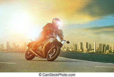 jonge man, paardrijden, groot, motorfiets, leunend, scherp, bocht, met, stedelijke , gebouw, achtergrond