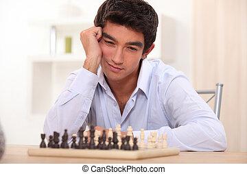 jonge man, schaakspel, spelend