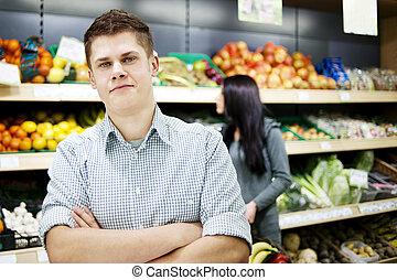 jonge man, staand, de, voorkant, van, shoppen , planken
