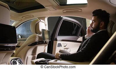 jonge, mannelijke , zakenman, het spreken op de telefoon, in, een, luxeauto
