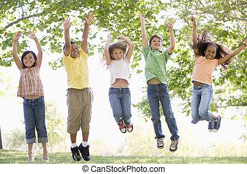 jonge, springt, vijf, buitenshuis, het glimlachen, vrienden