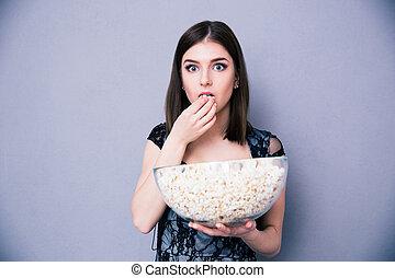 jonge, verbaasde vrouw, eten, popcorn