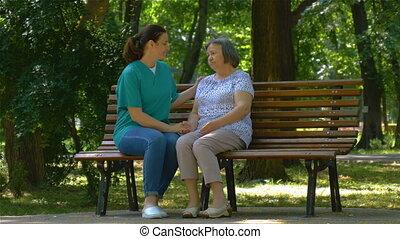 jonge, verpleegkundige, uitgeven, zonnige dag, met, oude vrouw, in park