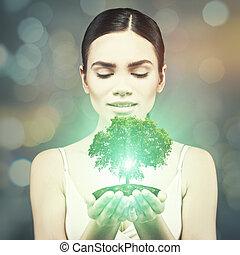 jonge volwassene, vrouw, houden, groen boom, op, zijn, handen