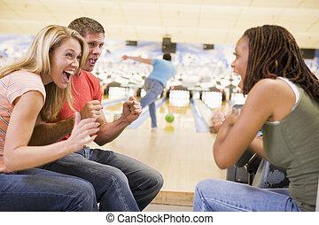 jonge volwassenen, juichen, in, een, bowling steeg