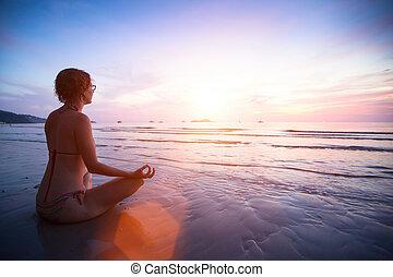jonge vrouw , beoefenen, yoga, op het strand, op, sunset.