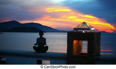 jonge vrouw , doen, yoga, oefening, in, en, meditates, op, een, achtergrond, sunset.