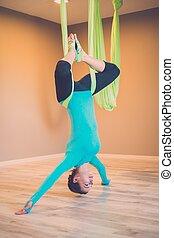 jonge vrouw , gedresseerd, antigravity, yoga, oefening
