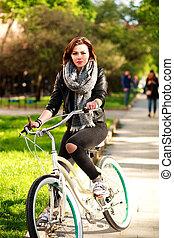 jonge vrouw , het berijden van een fiets, in, groene, stad park