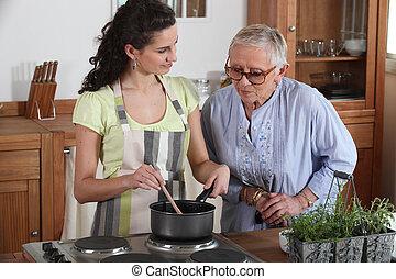 jonge vrouw , het koken, voor, een, bejaarden, dame