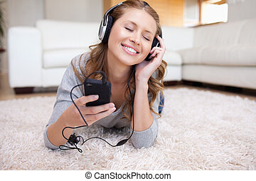 jonge vrouw , het liggen, op het tapijt, horende muziek