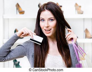 jonge vrouw , houden, kredietkaart, in, schoeisel, winkel