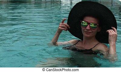 jonge vrouw , in, een, black , broad-brim, en, zonnebrillen, het rusten, in, zwembad