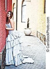 jonge vrouw , in, een, toga, leunend tegen de muur