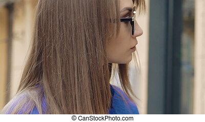jonge vrouw , in, zonnebrillen, gebruik, telefoon, en, kijken naar van fototoestel, buiten