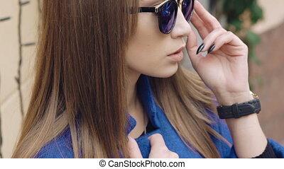 jonge vrouw , in, zonnebrillen, kijken naar van fototoestel, buiten