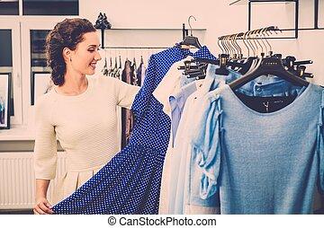 jonge vrouw , kies, kleren, op, een, rek, in, een, toonzaal