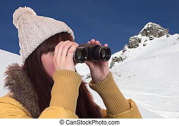 jonge vrouw , kijkend door verrekijkers, in de bergen