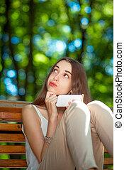 jonge vrouw , met, mobiele telefoon, in het park