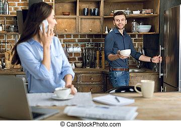 jonge vrouw , met, smartphone, en, koffiekop, kijken naar, man, met, kom
