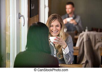 jonge vrouw , met, vriend, het hebben van koffie, op, koffiehuis