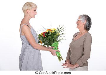 jonge vrouw , offergave, een, boeket van bloemen, om te, haar, grootmoeder