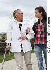 jonge vrouw , portie, oudere persoon, om te lopen, met, een, kruk